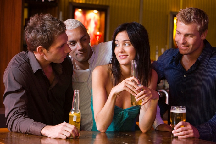 Men talking to woman at bar
