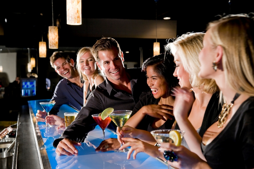 Group of people with drinks at nightclub bar, focus on couple in middle